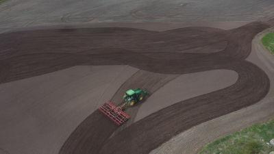En traktor med harv fotad från luften över en åker
