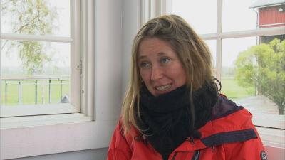 En kvinna med långt hår och röd jacka sitter intill ett fönster