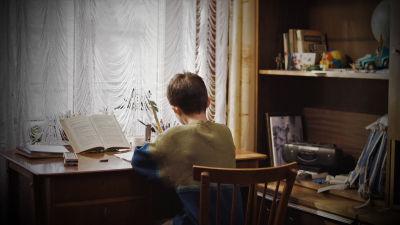 En pojke sitter vid ett skrivbord med ryggen vänd mot kameran.