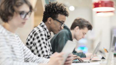 Opiskelijoita opiskelemassa kirjastossa.