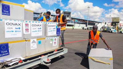 Lådor som innehåller coronavacciner flyttas på en flygplats.