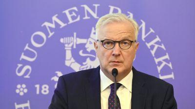 Olli Rehn, chefdirektör för Finlands Bank talar i en mikrofon under en presskonferens.