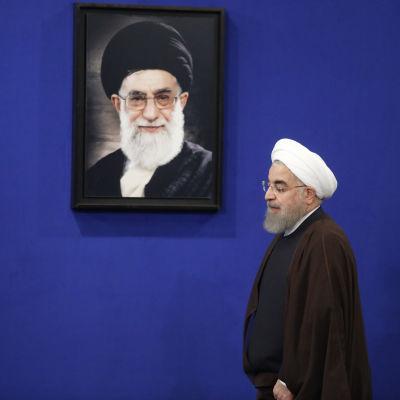 Ett arkivfoto på president Hassan Rouhani då han passerar ett porträtt av Irans högste ledare Ayatolla Ali Khamenei.