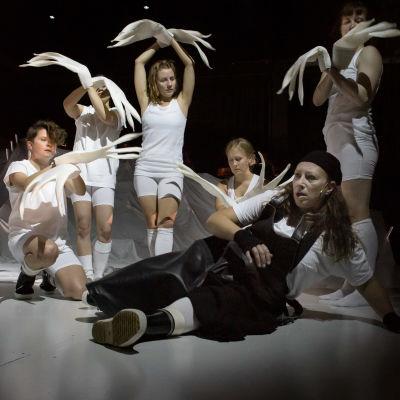 Fotografi från repetionerna av Kalevala på Åbo Svenska Teater. Stående skådespelare i vitt håller upp måsdockor i händerna.