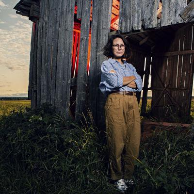 En kvinna står framför en förfallen lada.