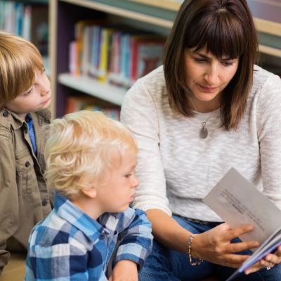En mamma läser högt ur en bok för två små pojkar.