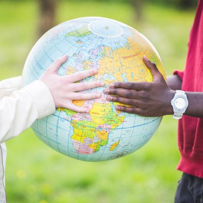 Två personer håller i en jordglob för att symbolisera invandring.