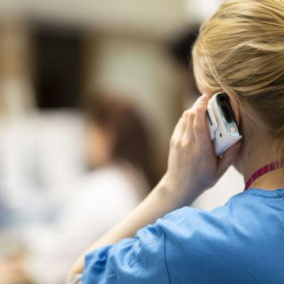 Hoitaja vastaa puheluun Lastensairaalan ensiavussa