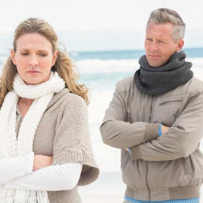 Kvinna och man på strand, hon står bortvänd från honom, båda har armarna i kors