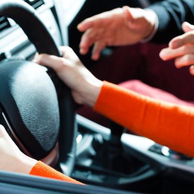 En ung kvinnas händer vid ratten på en bil med en äldre mans händer som gestikulerar från passagerarsätet.