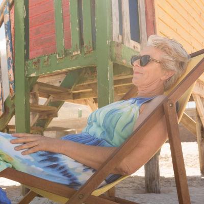 Äldre kvinna sitter i solstol och småler