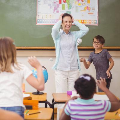 Kuvassa on päätään pitelevä opettaja luokassa. Oppilaat ovat selin kuvaan ja heittelevät paperipalloja opettajaa kohti.