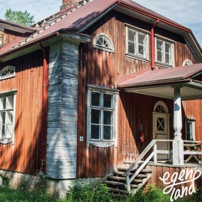 Varjakansaaren vanhan sahakylän asuinrakennus, punavalkoinen kaksikerroksinen puutalo, maali kulunut, autiotalo.