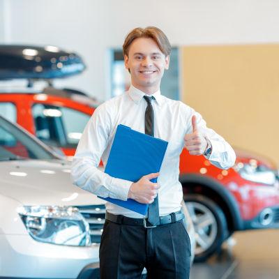 Autokauppias nostaa peukkua autojen edessä
