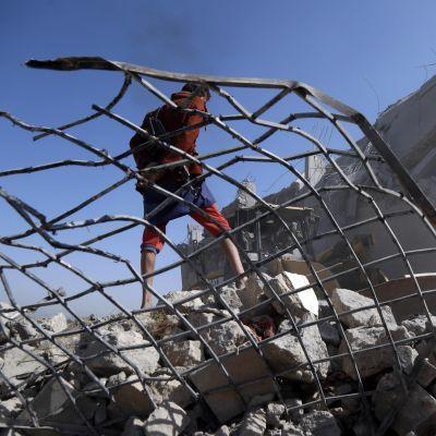 En man står på ruinerna av ett fängelse som bombats sönder i en saudiledd flygattack den 1 september.