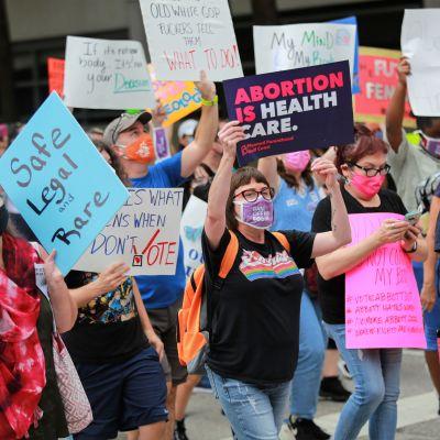 """Joukko naisia kulkee plakaattien kanssa. Keskellä kuvaa nainen pitelee kylttiä, jossa lukee englanniksi: """"Abortti on terveydenhuoltoa."""""""