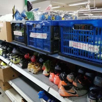 Kenkiä ja laatikoita hyllyissä.