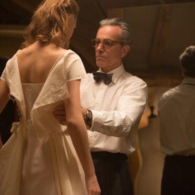 Reynolds Woodcock (Daniel Day-Lewis) står och mäter och provar ett tyg över Alma (Vicky Krieps) som står modell.
