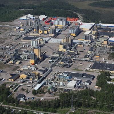 Flygbild över fabriksanläggning med byggnader och facklor.