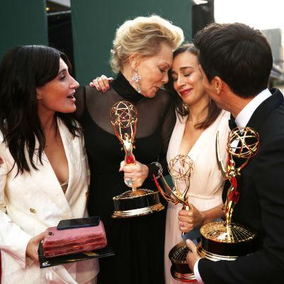 Ett gäng människor kramas med Emmystatyetter i armarna.