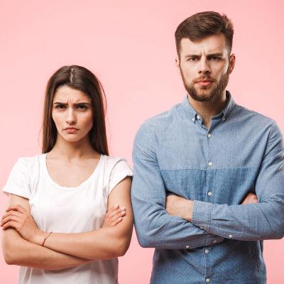 Ung man och kvinna med irriterade miner står framför rosa bakgrund
