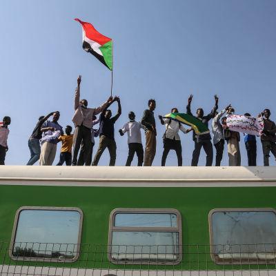 Folk står på rad på ett tåg, och en viftar med en flagga.