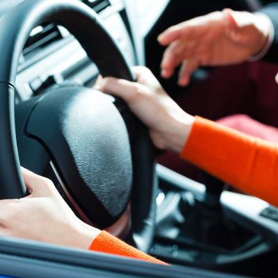 En ung person håller i en ratt och en bilskolelärare gestikulerar bredvid.