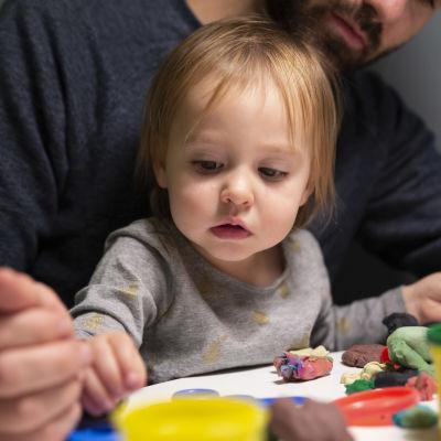 Ett och ett halvt-åriga Mathilda leker i pappas famn.