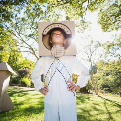 En pojke i astronautkläder står på en gräsmatta.