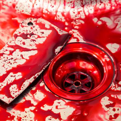 Blodig stor slaktarkniv ligger vid blodig golvbrunn.