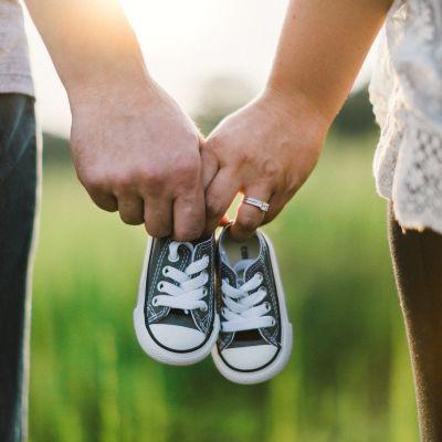 Ett par barnskor i händerna på en man och en kvinna. Illustrationsbild.