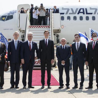 Bild på kostymklädda män poserar utanför ett vitt flygplan.