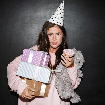 Tveksam ung kvinna med partyhatt och famnen full av paket
