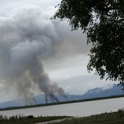 By brinner på andra sidan om floden som utgör gränsen mellan Bangladesh och Burma.