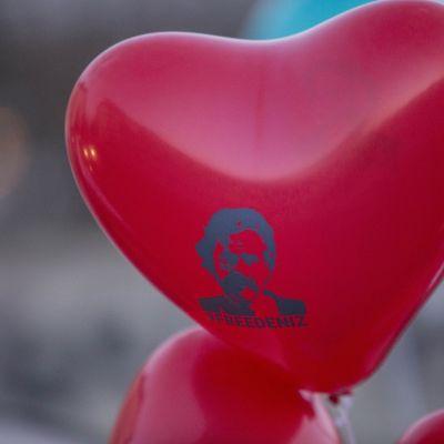 En röd hjärtformad ballong med bild på Denis Yücel och texten #freedeniz