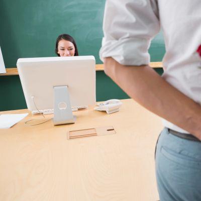 man som döljer rosor bakom sin rygg och tittar på en ung kvinna som jobbar vid sin dator