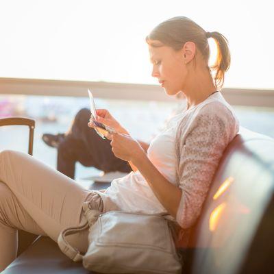 Kvinna som sitter på ett flygfält.