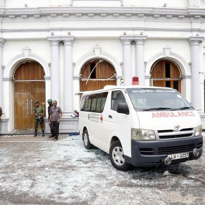 En ambulans står parkerad utanför ett hotell som utsatts för en explosion. Flera beväpnade poliser syns på bilden och marken är täckt av glassplitter.