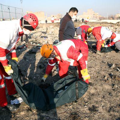 Kansainvälisen Punaisen puolikuun työntekijät tutkivat koneen jäänteitä keskiviikkona onnettomuuspaikalla.
