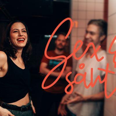 Malena Holmström står i en mörk pubb. Hon har på sej en svart topp och gröna byxor. Malena Har brunt hår och rödmålade läppar och ser glad ut.