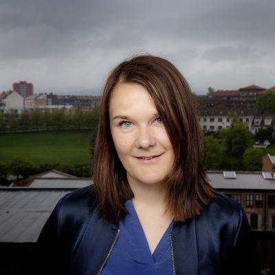 Porträttbild av Marie Aubert som tittar rakt in i kameran med höghus och en park i bakgrunden.