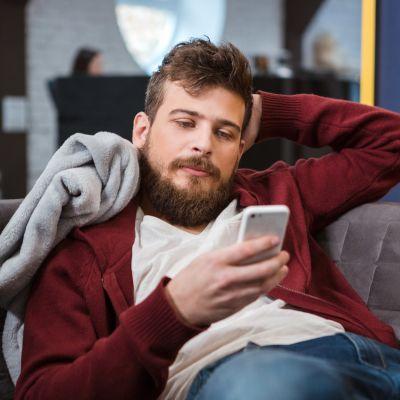 Man halvligger i soffa och ser på sin telefon