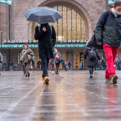 Ihmisiä kävelemässä Helsingin päärautatieaseman sisäänkäynnin edustalla.