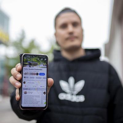 Joni Parviainen pitää kädessään kännykkää, jossa on auki Salon seudun puskaradio -ryhmä.