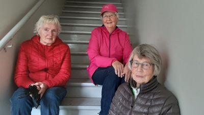 Tre damer sittandes i trappa