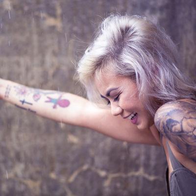 En skrattande kvinna räcker ut sin arm.