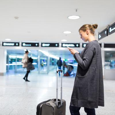 En kvinna står på ett flygfält och tittar på sin mobil, med kappsäcken framför sig.