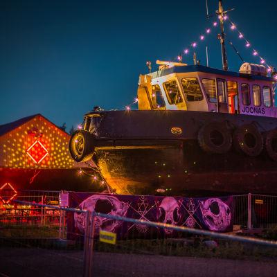 Upplyst båt och varvsbyggnad på H2Ö-festivalen.