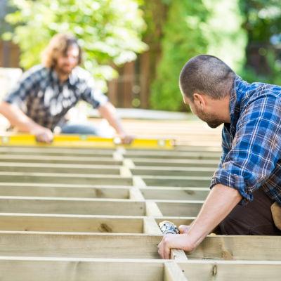 En man står med handen på en träplanka på en byggarbetsplats.