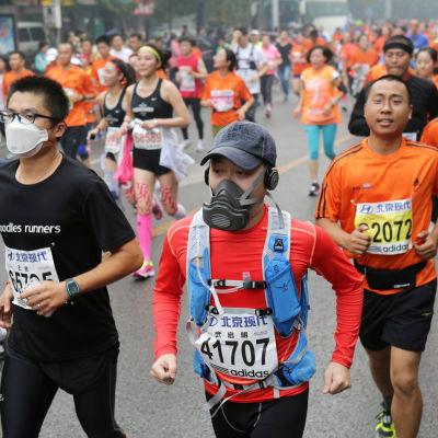 Kineser med andningsskydd springer maraton.
